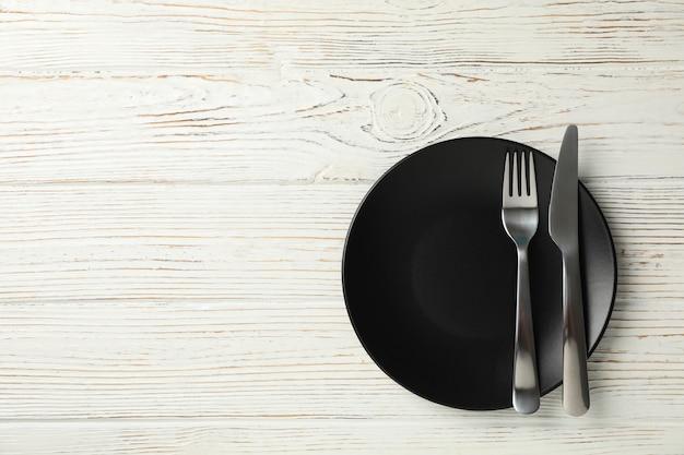 Talerz z widelcem i nożem na drewnianym