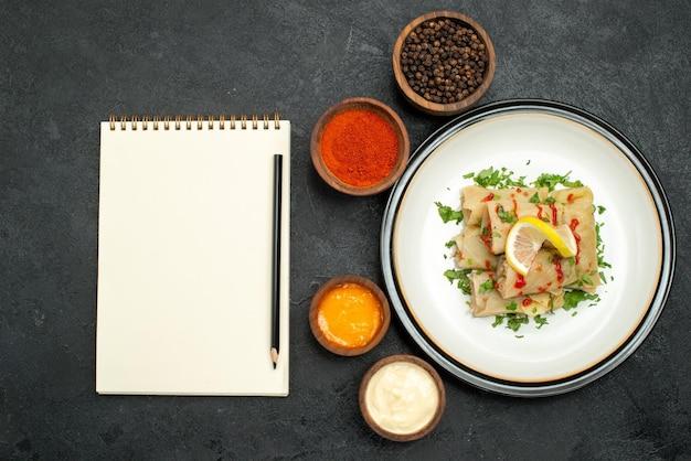 Talerz z widokiem z góry i zeszyt faszerowana kapusta z ziołami cytrynowymi i talerz z sosem obok białego zeszytu