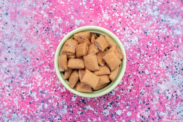 Talerz z widokiem z góry z poduszką z chipsami w kształcie słodkich krakersów wewnątrz zielonego talerza na kolorowym biurku w kolorze słodkiej cukrowej przekąski