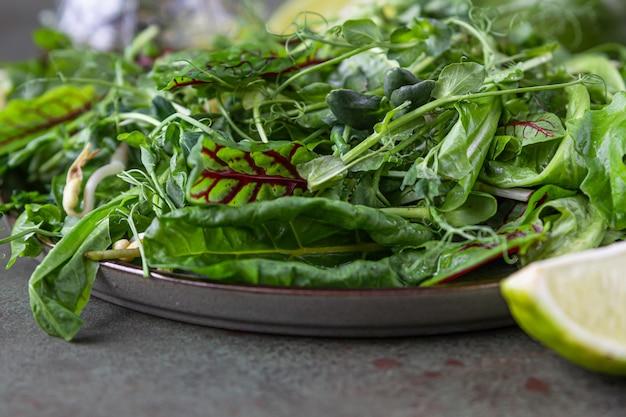 Talerz z zielonymi liśćmi sałaty i mikro zieleniną, limonką, awokado i oliwą z oliwek