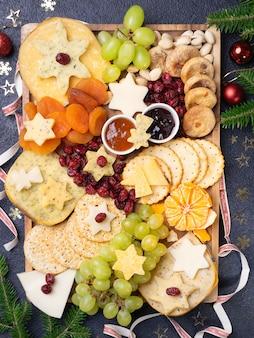 Talerz zakąsek z różnymi rodzajami sera, winogron, suszonych fig, żurawiny, pistacji i dżemów