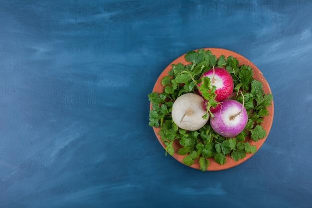 Talerz zdrowych rzodkiewek białych i czerwonych z zieleniną na niebieskim tle.