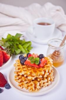 Talerz ze słodkimi smacznymi goframi z miodem, jagodami, filiżanką herbaty