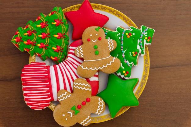 Talerz ze smacznymi świątecznymi ciasteczkami świątecznymi w kształcie choinki, piernika, gwiazdy i świątecznej skarpety na drewnianym stole. widok z góry