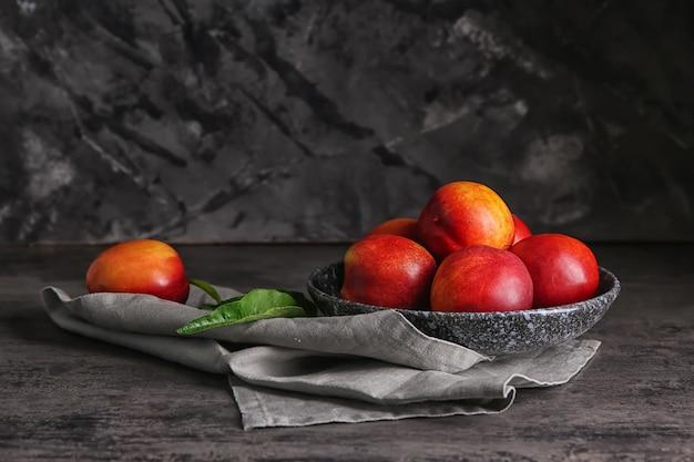 Talerz ze świeżymi brzoskwiniami na ciemnym stole