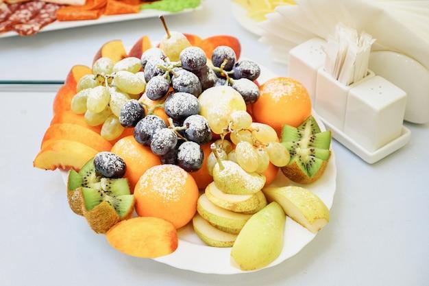 Talerz ze świeżymi mieszanymi owocami na stole w kawiarni