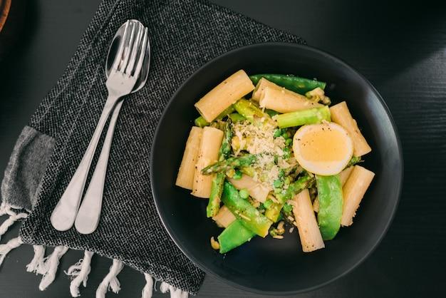 Talerz ze szparagami makaronu i jajkiem na czarnym stole