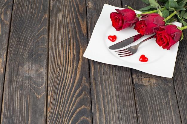 Talerz ze sztućcami, trzy czerwone róże i czerwone serca