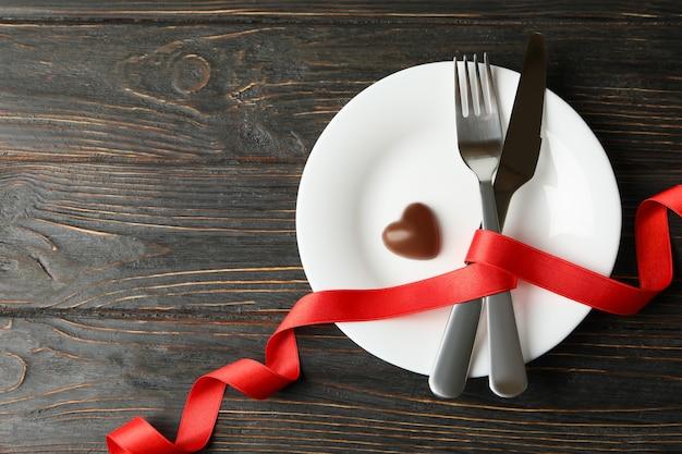 Talerz ze sztućcami, wstążką i czekoladowym sercem na podłoże drewniane