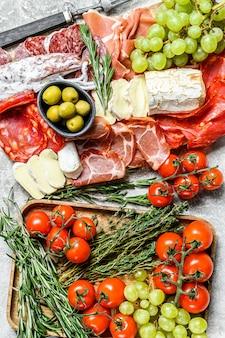 Talerz zestawu antipasto. talerz mięsny wędzony na zimno z kiełbasą, szynką w plasterkach, szynką parmeńską, boczkiem, oliwkami. różnorodność zakąsek. szare tło. widok z góry