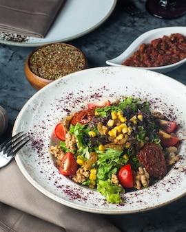 Talerz zielonej sałatki z sałatą pomidorową kukurydzianą i rodzynkami