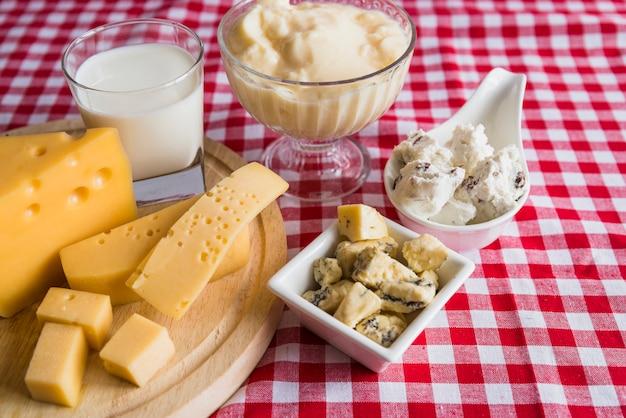 Talerze i deska do krojenia ze świeżym serem w pobliżu kieliszka napoju