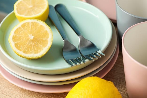 Talerze i filiżanki z cytrynami brogującymi na drewnianym stole, zamykają up