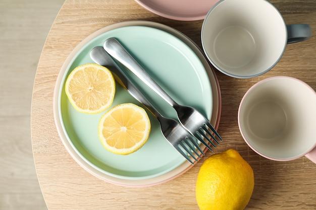 Talerze i filiżanki z cytrynami na drewnianym stole, widok z góry