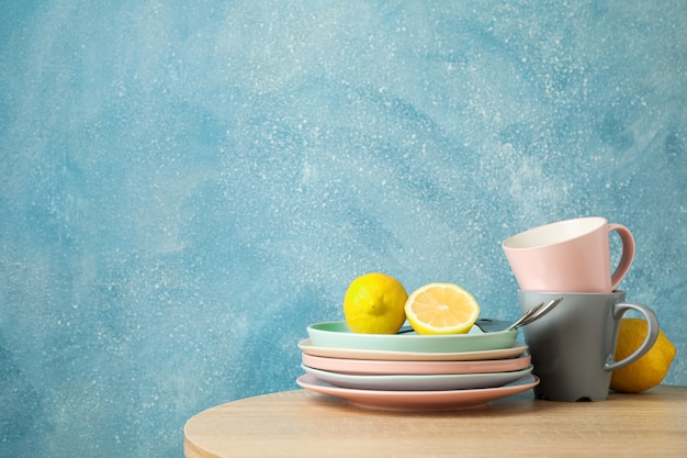 Talerze i filiżanki z cytrynami ułożone na drewnianym stole, miejsca na tekst