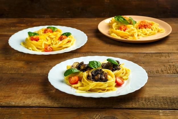 Talerze na stole z gniazdami makaronu nadziewane mieszanką serów pasta makaronowa z wiśniami