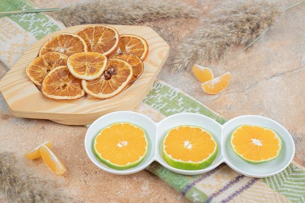 Talerze plasterków cytryny i suszonej pomarańczy na marmurowej powierzchni.