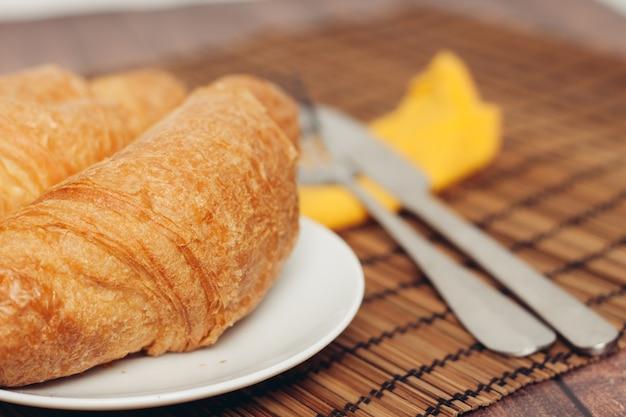Talerze rogalików na drewnianym stole kuchnia śniadanie świeży zapach. wysokiej jakości zdjęcie
