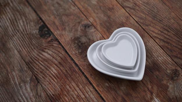 Talerze w kształcie serca na drewnianym tle - koncepcja 14 lutego