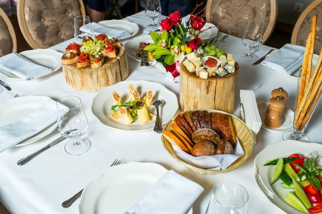 Talerze z zimnymi przystawkami i serem w plasterkach na stole do serwowania