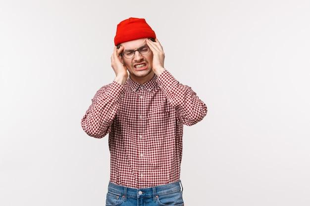 Talia portret mężczyzny cierpiącego na wielką migrenę, chwyć głowę dotykając świątyń zamkniętymi oczami i wykrzywiając się z bólu, bolesny ból głowy, gdy przyjaciel zbyt głośno słucha muzyki, stoi