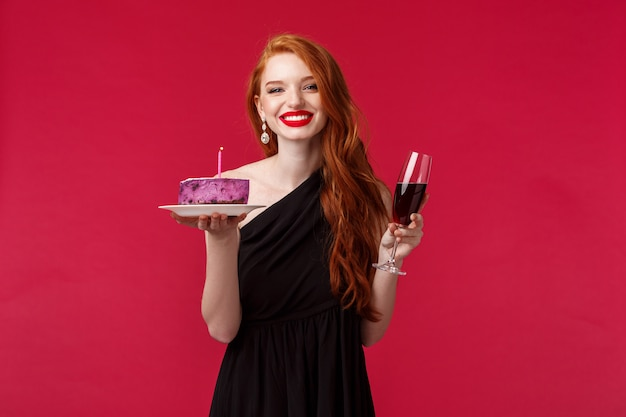 Talia-portret przepięknej kobiecej młodej rudej kobiety świętującej urodziny, popijającej kieliszek wina i trzymającej tort z zapaloną świecą uśmiechającą się jako spełnianie marzeń