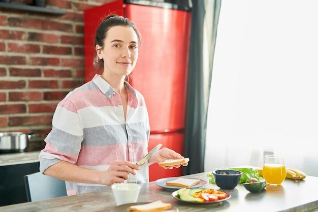 Talia się portret uśmiechnięta młoda kobieta patrząc na kamery podczas gotowania zdrowego śniadania w nowoczesnym mieszkaniu, miejsce
