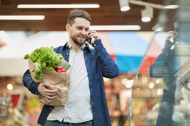 Talia się portret uśmiechnięty brodaty mężczyzna dzwoni przez smartfona podczas zakupów w supermarkecie