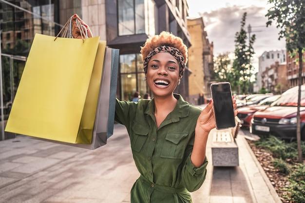 Talia się szczęśliwa afro american kobieta pokazuje torby na zakupy i telefon komórkowy w mieście