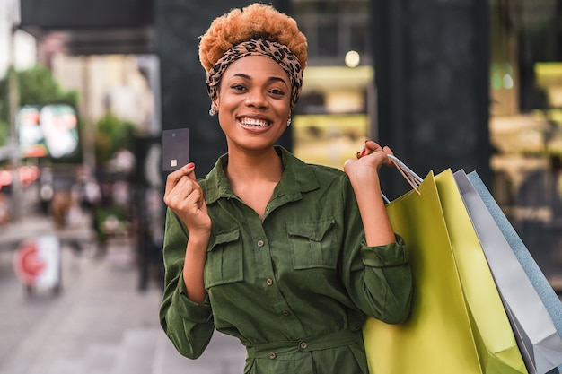 Talia się szczęśliwa młoda kobieta z torby na zakupy na ulicy miasta, trzymając czarną kartę debetową