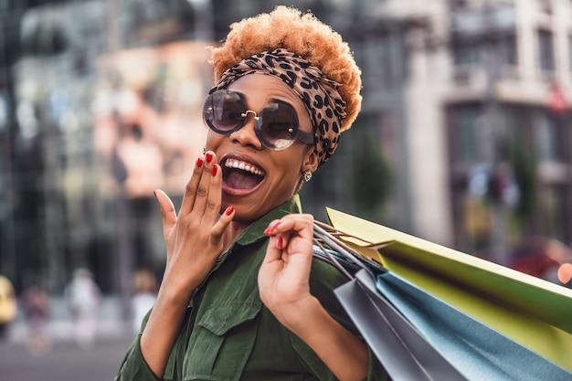 Talia się uśmiechnięta ładna kobieta w okularach przeciwsłonecznych i chodzenie po ulicy, trzymając torby na zakupy