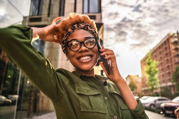 Talia szczęśliwy całkiem afro american kobieta i okulary stojąc na zewnątrz podczas rozmowy przez telefon komórkowy