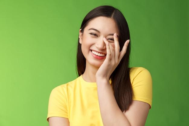 Talia-up szczera szczęśliwa wesoła delikatna kobieca azjatycka brunetka, śmiejąca się beztrosko uśmiechnięta, ciesząca się zabawnym towarzystwem, chichocząc, dotykając twarzy nieśmiała rumieniąc się słodkie komplementy, zielone tło.