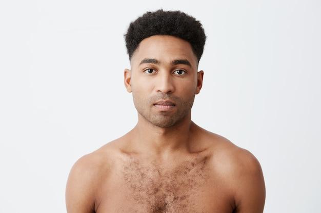 Talia w górę portret poważnego czarnoskórego mężczyzny rasy mieszanej rasy afrykańskiej z kręconymi ciemnymi włosami bez ubrań, patrząc w kamerę z zrelaksowanym wyrazem twarzy.