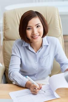 Talia w górę portreta azjatycka biznesowa kobieta siedząca na biurowym krześle robi notatkom w papierach