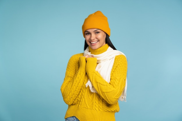 Talia w górę widok portretu pozytywnej kobiety w żółtym swetrze stojącej z uśmiechem, wyglądającej na szczęśliwą i zadowoloną, trzymającej ręce razem. kryty studio strzał na białym tle na niebieskim tle