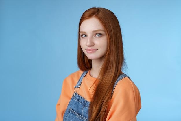 Talii-up miły szczery delikatny piękny rudowłosy dziewczyna ubrana w pomarańczową koszulę drelichowe kombinezony stojąca na wpół odwrócona uśmiechnięta głupia, łagodna kamera uśmiechnięta, patrząca przyjaźnie, przyjemnie chodzić samotnie na niebieskim tle.