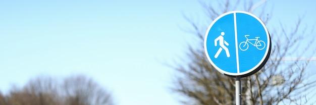 Tam jest znak dla pieszych i rowerzystów na ulicy. znak dla pieszych i rowerzystów z rozdzieleniem ruchu. ścieżki oznaczeniowe przeznaczone dla pieszych i rowerzystów o wspólnym ruchu