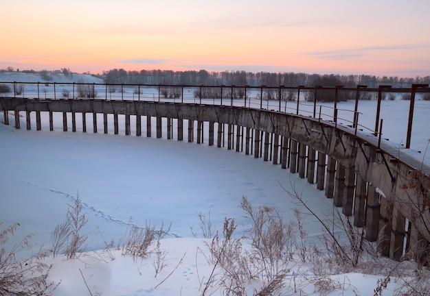 Tama na stawie w zimowy poranek łuk betonowej tamy na zimowym stawie w pobliżu nowosybirska