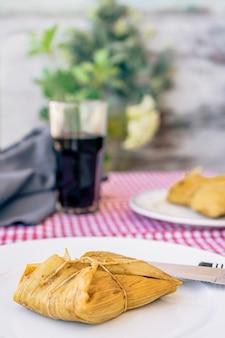 Tamale podawane na białym talerzu na tradycyjnym stole obok kieliszka czerwonego wina. typowa kanapka lub latynoamerykański posiłek złożony z mąki kukurydzianej i mięsa. tradycyjne andyjskie jedzenie. skopiuj miejsce
