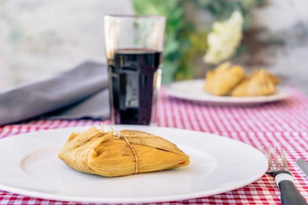 Tamale podawane na białym talerzu na tradycyjnym stole obok kieliszka czerwonego wina. typowa kanapka lub latynoamerykański posiłek złożony z mąki kukurydzianej i mięsa. tradycyjne andyjskie jedzenie. tradycyjna koncepcja żywności