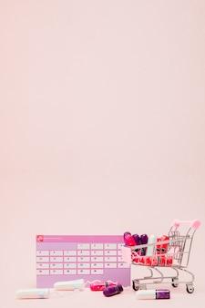 Tampon, kobiece, podpaski higieniczne na krytyczne dni, kobiecy kalendarz, tabletki przeciwbólowe podczas menstruacji na różowym tle. śledzenie cyklu miesiączkowego i owulacji