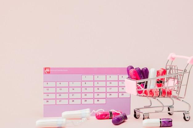 Tampon, kobiece, podpaski na krytyczne dni, kalendarz kobiecy, tabletki przeciwbólowe w okresie menstruacji na różowym tle. śledzenie cyklu miesiączkowego i owulacji.