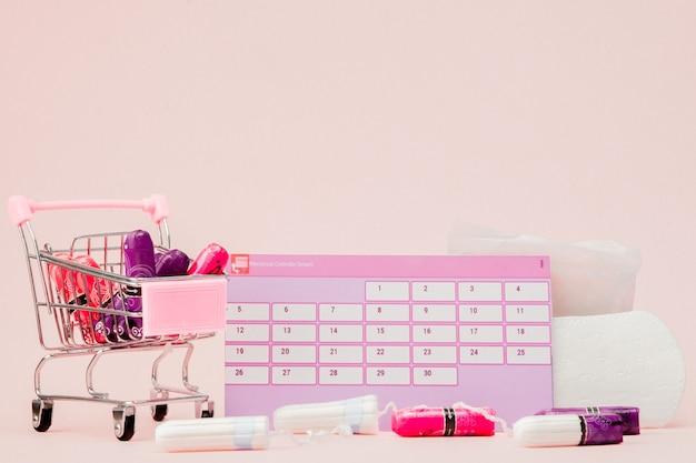 Tampon, kobiece, podpaski na krytyczne dni, kalendarz kobiecy, tabletki przeciwbólowe w okresie menstruacji na różowym tle.