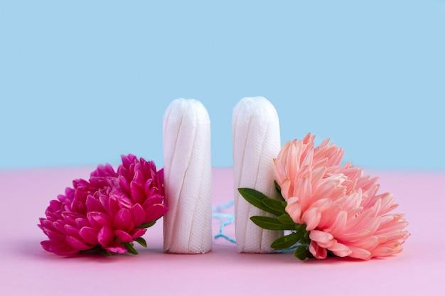 Tampony na krytyczne dni i kwiaty na różowym stole. higiena w czasie menstruacji. cykl miesiączkowy. w trosce o zdrowie kobiet. comiesięczna ochrona
