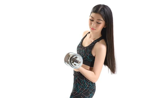 Tan skin asian fitness girl w sexy cute sport bra czarne spodnie spandex ćwiczenia rozgrzewki. ćwicz postawę podnoszenia hantli. przez pojedyncze białe tło.