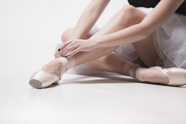 Tancerka baleriny siedzi ze skrzyżowanymi nogami