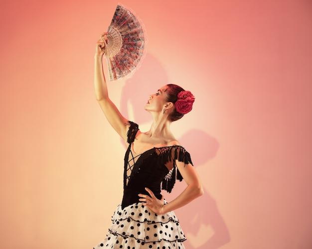 Tancerka flamenco. hiszpania cyganka z czerwoną różą i hiszpański wentylator strony pozowanie i taniec w studio. namiętny hiszpański temperament i pasja w tańcu. koncepcja ludzkich emocji