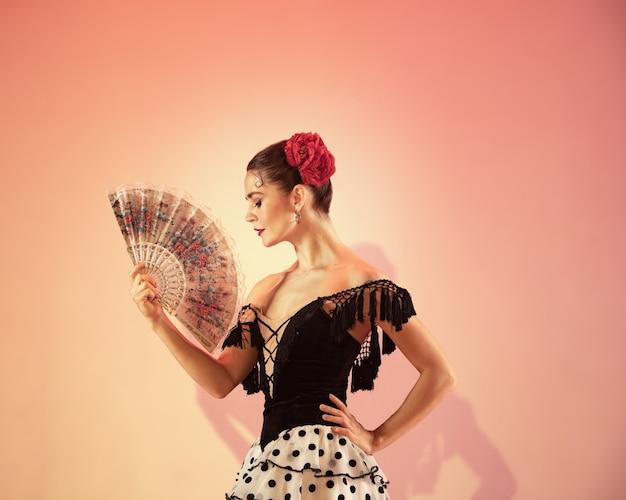Tancerka flamenco hiszpania cyganka z czerwoną różą i hiszpańskim wachlarzem pozuje i tańczy w studio