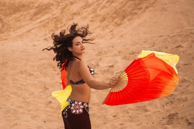 Tancerka na pustyni z jedwabnymi tkaninami.